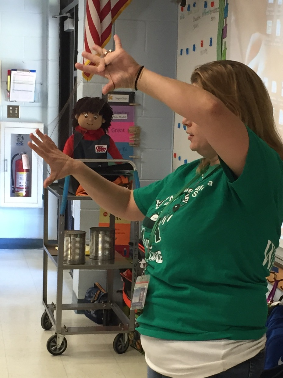 Amanda Nash holds up a disposable hair net and explains to students why it's important for her to wear one while in the school's kitchen.