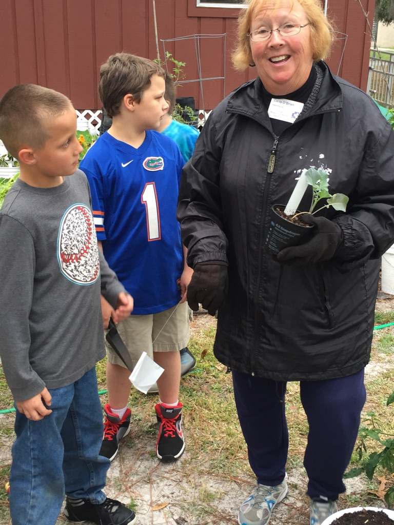 Carla O'Brien talks with a couple of third grade boys about planting in the soil.