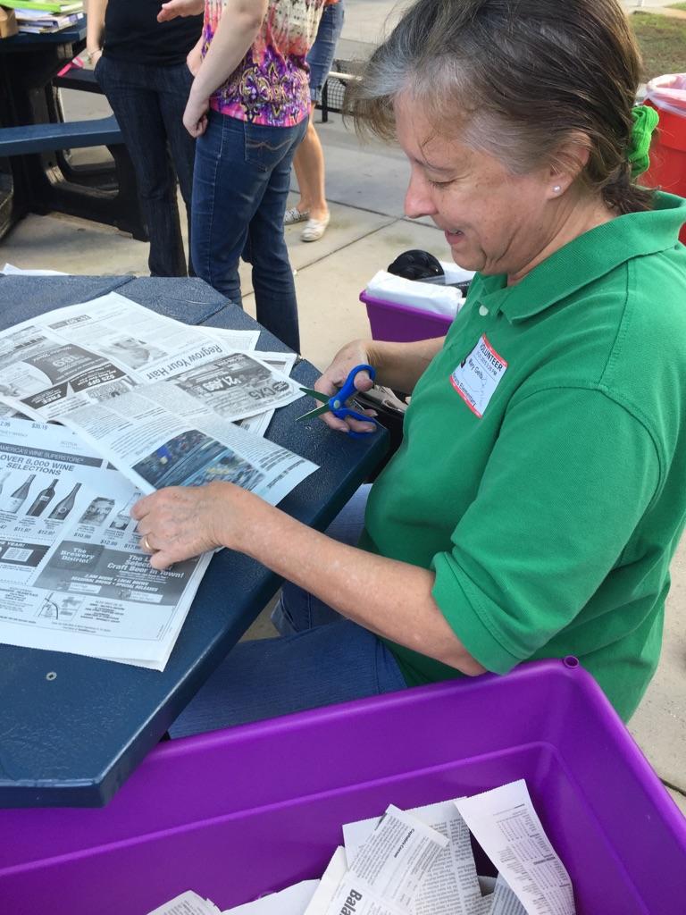 Denise Gelb cuts newspaper into scraps.