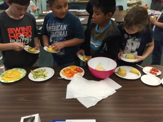 Students taking part in a healthy snack- a colorful array of fruits and vegetables which included avocado, red, orange and yellow peppers, mangoes and bananas.