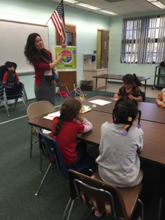 Ms. Villegas holding up a MyPlate poster as she talked about the five food groups with a group of students.
