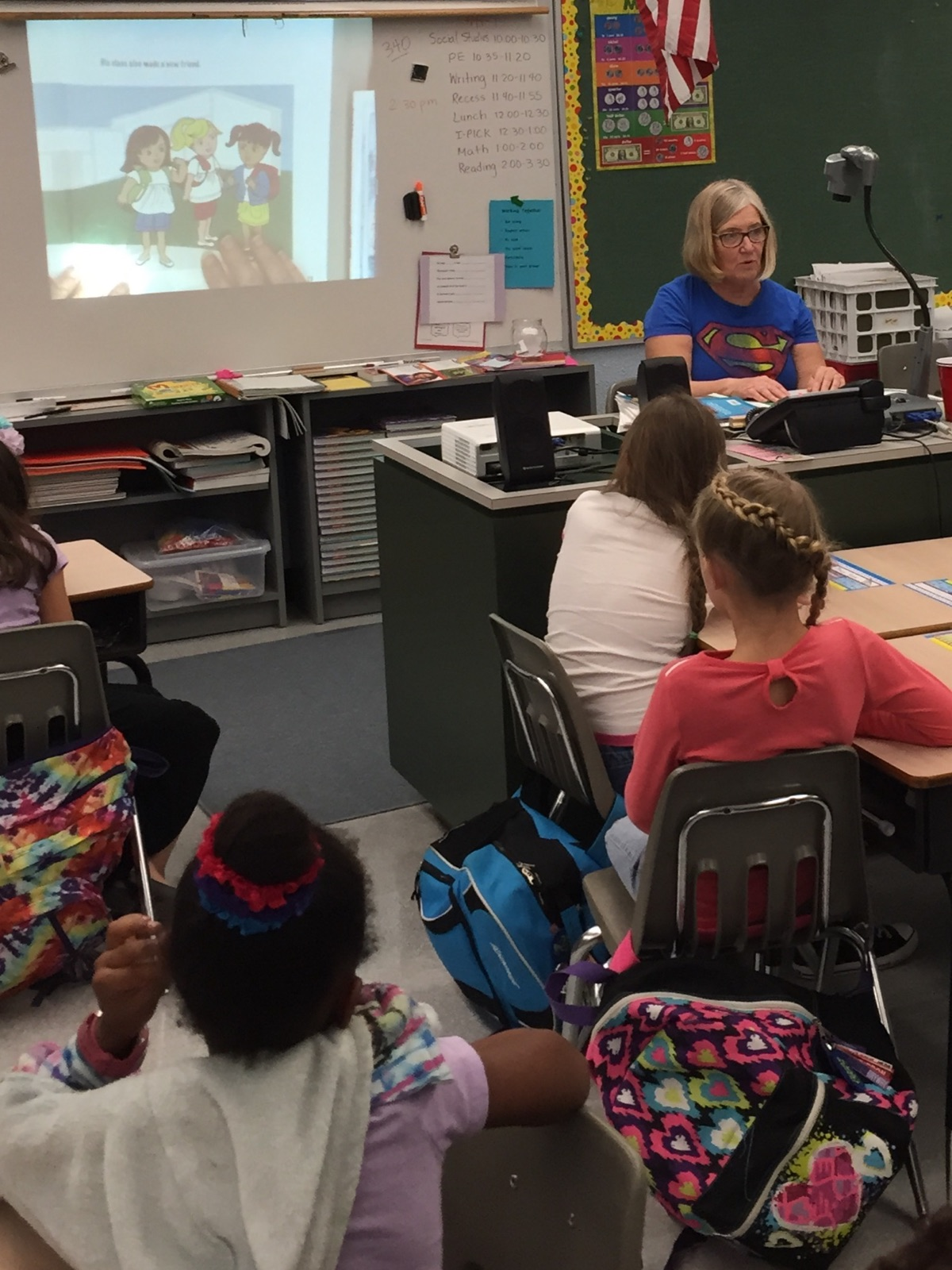 Ms. Suzanne reading to second graders, showing pictures of the story on the overhead projector.