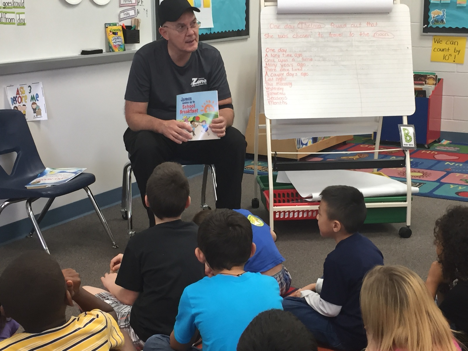 Mr. Stan shows first graders the cover of the book James Wakes Up to School Breakfast before beginning the story.