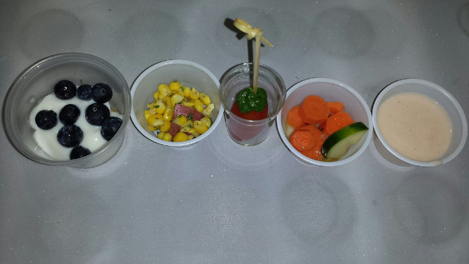 Fresh fruit and vegetable recipes prepared by Chef Paula. From right to left: Blueberry and Yogurt Breakfast Cups, Corn and Potato Salad, Grapes Tomatoes with Spinach Arugula Pesto, Marinated Carrot and Cucumber Salad and Cantaloupe Smoothie.